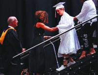 <p>Special-education aide Heather Miller helps Rachel Barezinsky off the stage during Thomas Worthington High School's commencement last month. Although Rachel could have graduated, she didn't so that she would be eligible for special-education classes this fall.</p>